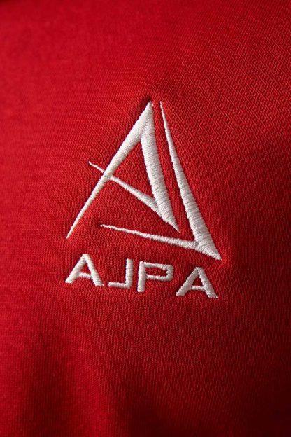 logo ajpa na bluzie czerwonej z kapturem rozpinana